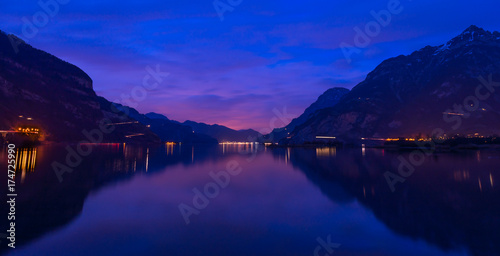 Foto op Aluminium Donkerblauw Central Switzerland, Lake Lucerne. Night landscape. Royal blue. The mountain range, the light of lanterns and lamps are reflected in the lake, long exposure