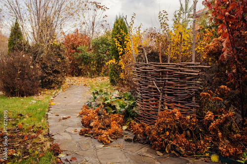 Walking in november garden. Late autumn view with rustic fence and stone pathway - 174726195