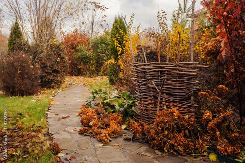 Zwiedzanie ogrodu w listopadzie. Opóźniony jesień widok z wieśniaka ogrodzeniem i kamienna droga przemian