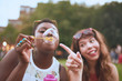 group of two diverse friends blowing soap bubbles at a summer music festival.
