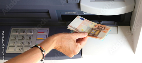 girl while withdrawing 50 euros banknotes  from an ATM - 174736554