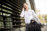 Young successful man  executive businessman using his mobile cell phone near office building - 174737503