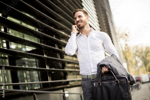Naklejka Young successful man  executive businessman using his mobile cell phone near office building