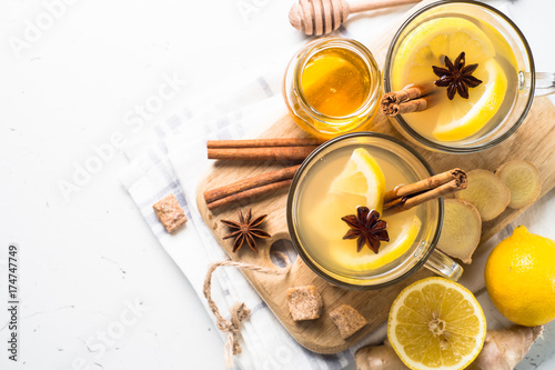 Hot Ginger tea with lemon, honey and spices. Top view with copy space on white.