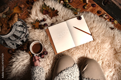 Tuinposter Herfst Relaxing autumn day at home with coffee and blank notebook for copyspace in warm coziness scandinavian hygge style, POV first person look which is female