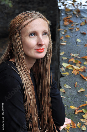 Keuken foto achterwand Kapsalon Woman in sad mood against the background of autumn leaves. Woman with a hairstyle from wattled braids