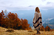 Hiker girl wrapping in warm poncho outdoor. Young woman hiking at mountain peak