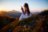 A girl sits on the edge of the cliff and looking at the sun valley and mountains. Woman sitting on mountain top and contemplating the sunset. Young woman in long white dress