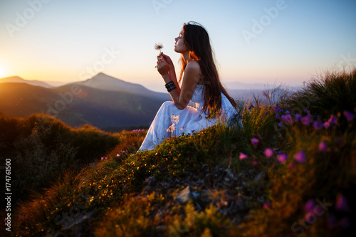 Foto op Aluminium Chocoladebruin A girl sits on the edge of the cliff and looking at the sun valley and mountains. Woman sitting on mountain top and contemplating the sunset. Young woman in long white dress