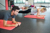 group of people practicing the side plank yoga pose - 174763187