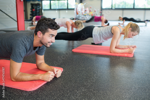 group of people practicing the side plank yoga pose