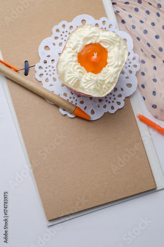 Blank notebook with pen and cupcake on wooden table. Poster