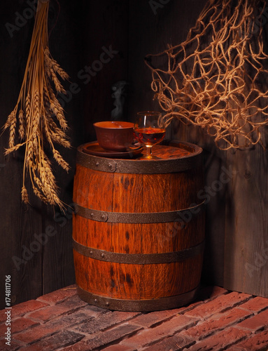 Glass of cognac with barrel in cozy cellar Poster