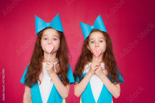 funny twins with a big bow holding lollypops Poster