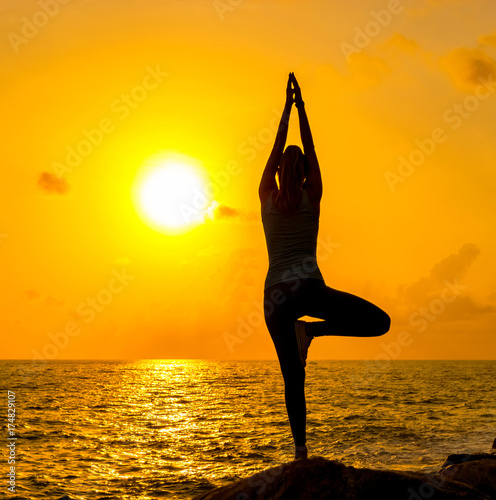 Fotobehang School de yoga A young woman is practicing yoga on the rocks by the sea against the background of the sun