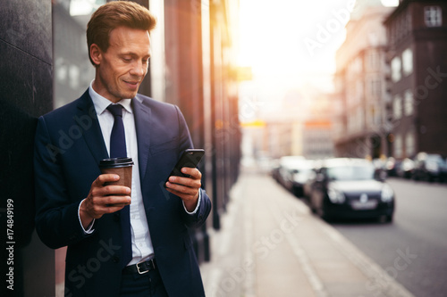 Smiling businessman reading messages and drinking coffee in the