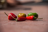 Variety of hot peppers in a small wicker basket - 174873742