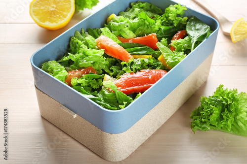 Delicious salad with salmon in lunch box on table © Africa Studio