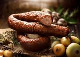 Smoked  sausage on a wooden rustic table with addition of fresh aromatic herbs and spices, natural product from organic farm, produced by traditional methods - 174885955
