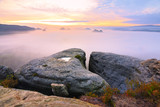 Autumn landscape. Morning view over sandstone cliff into deep misty valley. Sandstone peaks - 174903562