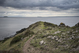 Moody landscape looking out to sea from headland during Autumn stormy weather - 174908560