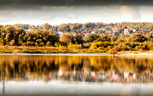 Tuinposter Herfst Beautiful river bank, autumn landscape with dramatic sky at sunset with reflection in water