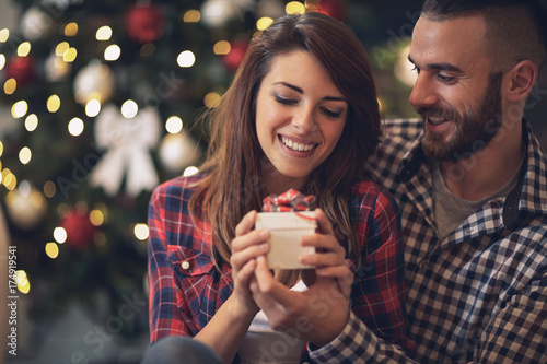 Woman with husband looking at Christmas gift