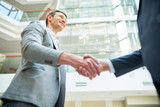 Low angle view of smiling business partners shaking hands while standing at spacious modern office lobby - 174919907