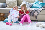 Portrait of two cute little girls playing together sitting on thick carpet at home, using digital tablet and coloring pictures - 174921398