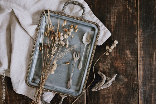 Still life with elegant fancy vintage tray with silver cutlery, dried beautiful and tiny field flowers and linen light grey napkin on brown old wooden dark table background Poster