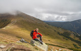 hiker sitting on rock builder in mountains - 174922963