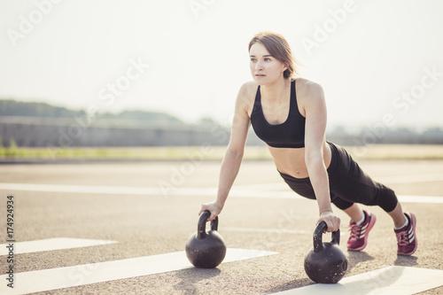 Slim brunette doing push-ups exercises on kettlebells. Cross fit training