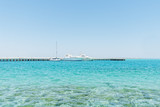 Three large white boats moored in the Red Sea under a blue sky. - 174925731
