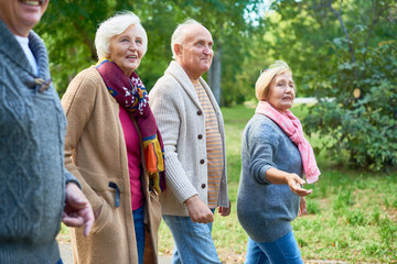 Elderly friends wearing knitted sweaters enjoying fresh air and picturesque view while walking along park alley