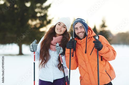 Joyful amorous couple of skiers in winterwear looking at camera
