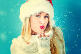 Happy young woman with Santa hat blowing snow - 174942148