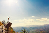 Man at the edge of a cliff overlooking the mountains below  - 174943531