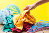 Pile of dirty laundry in washing basket on wooden,yellow background. - 174961727
