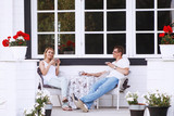 Happy young couple sitting and drinking tea on the porch - 174964737