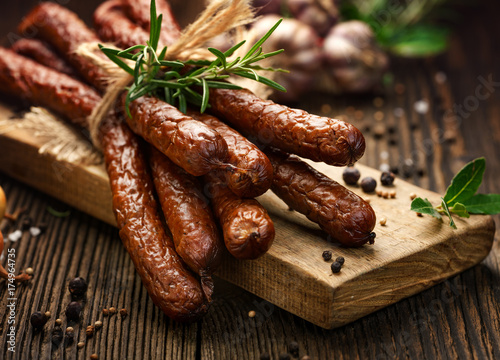 Kabanosy, polish sausages made of pork on a board with addition of fresh herbs and spices - 174964735