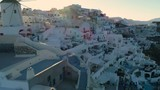 Flying above white houses and famous old castle ruins on Santorini Island, Greece. Village of Oia. Morning sunshine rays. - 174969757
