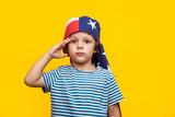 Boy giving salute on orange - 174972955