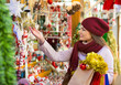 Smiling young woman choosing Christmas decoration