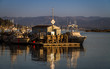 Marine vessels moored in the harbor with golden reflections in the setting sun