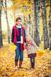 Smiling little girl and her mother enjoy walk in autumn park and play with bright autumn leaves - 174988325