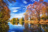 Sunny autumn landscape with blue sky over the lake - 174989339
