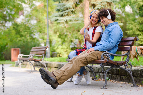 Fotobehang Muziek Young man and woman with headphones listening music outdoors in park