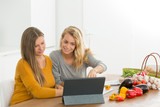 female friends cooking together following recipe on tablet - 174991527