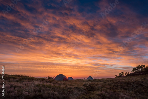 Bright Orange Clouds Glow Above Three Tents