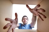 Young man is stretching hands into cardboard box. - 174996948